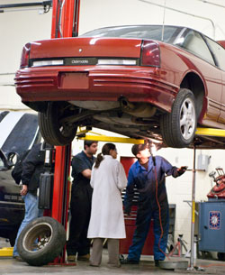 auto repair students listen to their instructor in a lab at the COT