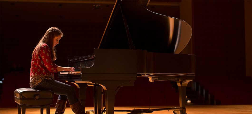 Student playing a grand piano in a concert hall