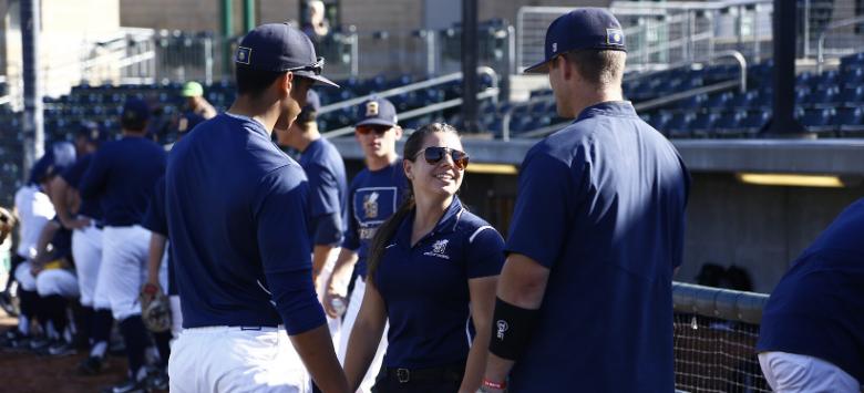 Athletes and trainer at a baseball game