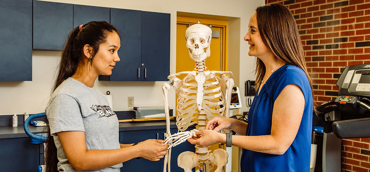 An instructor with a student in front of a model skeleton.