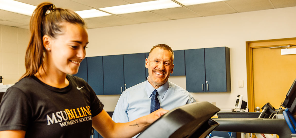 An instructor and student operate a treadmill.