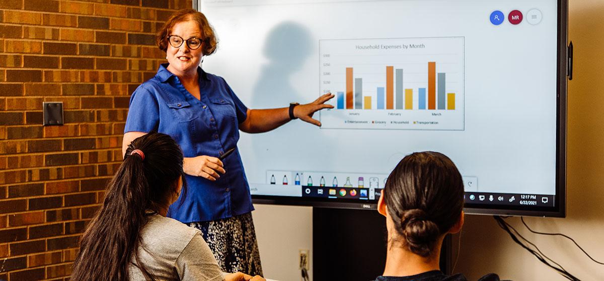 An instructor shows a bar graph on a screen