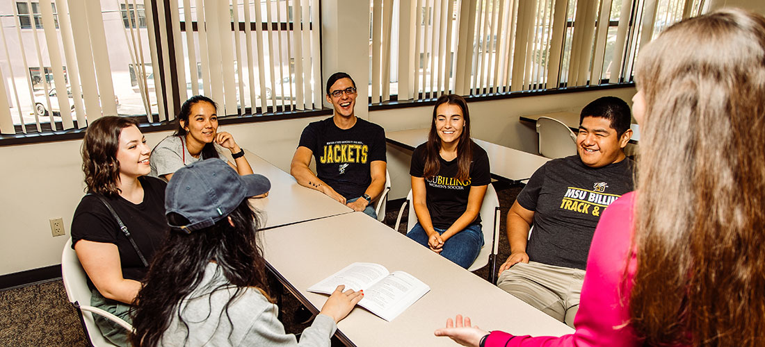 An instructor stands at a table of students