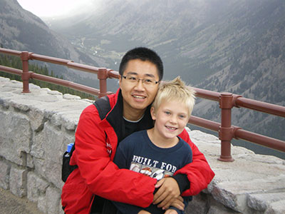 A student poses with a youth near a mountain range