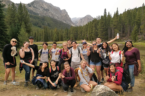 A group of students pose in front of a mountain