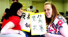 Emily and and friend writing in Japanese dou itashimashite (thank you)