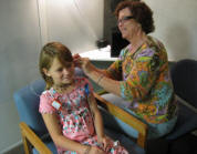 Photo of audiologist checking Abby's hearing